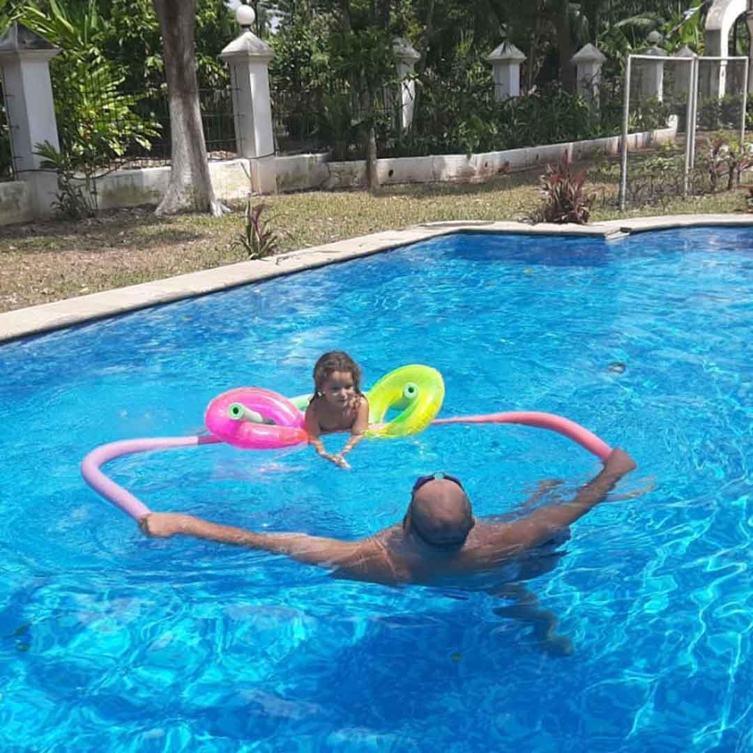Padre e hija jugando en alberca con flotadores